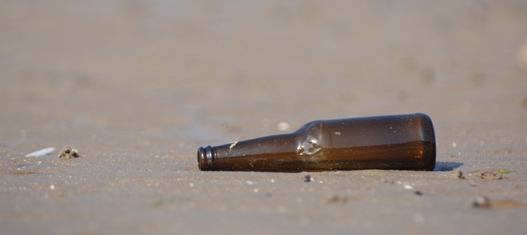 Photo of an empty beer bottle on the beach