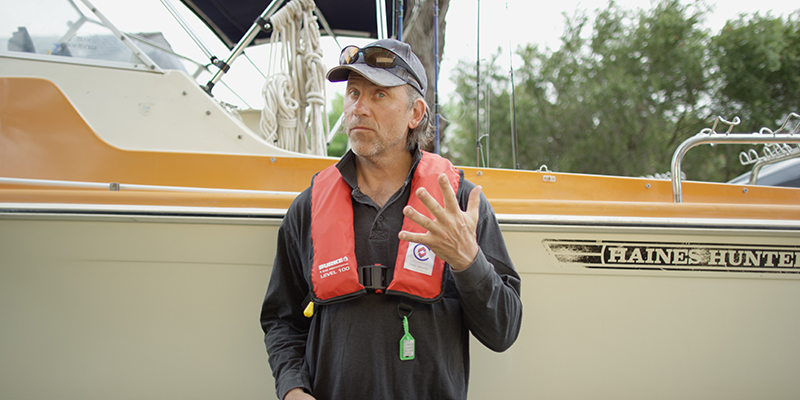 Man in lifejacket holding up five fingers
