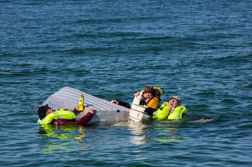 Three men in water cling to capsized boat