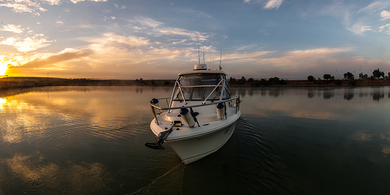 A boat on calm water at sunset