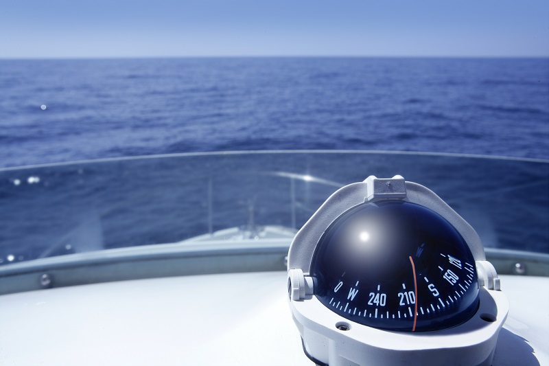 Compass on deck of boat with sea behind