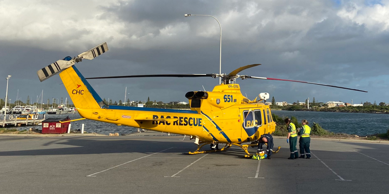 People standing next to a rescue helicopter