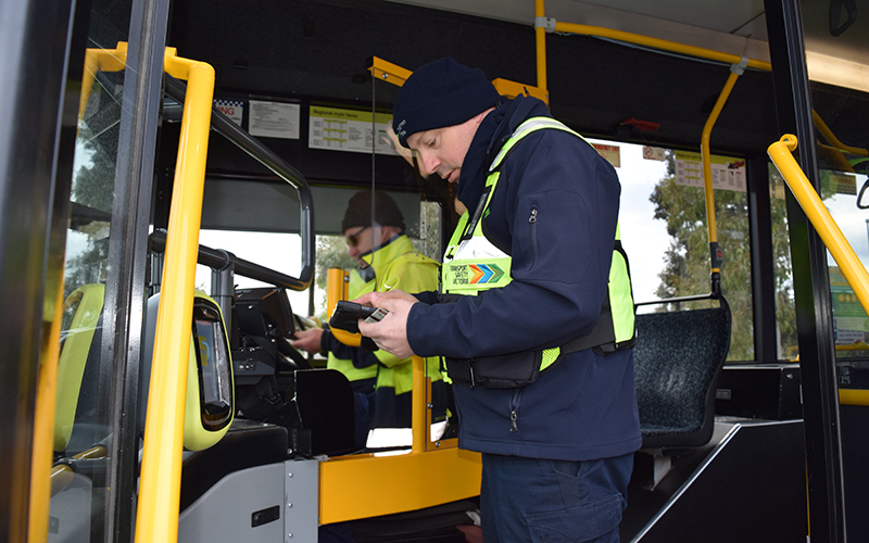An officer speaks to a bus driver
